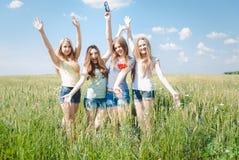 Quatre jeunes amis ayant l'amusement en été dehors Images stock