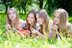 Quatre jeunes amis ayant l'amusement mangeant la fraise Photographie stock libre de droits