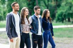 Quatre jeunes amis de sourire détendent en parc Images libres de droits
