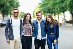 Quatre jeunes amis de sourire marchant sur la rue le jour chaud Photographie stock