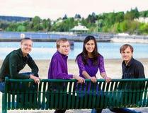 Quatre jeunes amis ethniques multi ensemble à la plage Photographie stock libre de droits