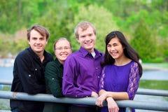 Quatre jeunes amis ethniques multi ensemble dehors par le lac Image libre de droits