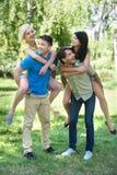 Quatre jeunes amis gais ayant l'amusement dans la PA Photos stock