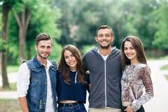 Quatre jeunes amis gais marchant le jour chaud Image stock