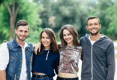 Quatre jeunes amis gais marchant le jour chaud Images libres de droits