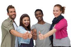 Quatre jeunes amis heureux faisant des gestes des pouces  Image libre de droits