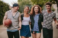 Quatre jeunes amis marchant ensemble et souriant Photo stock