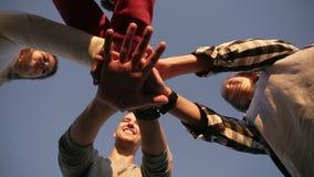 Quatre jeunes amis regardant vers le bas sur la terre posant le jour ensoleillé, mettant la main en main Team le travail Jeunesse banque de vidéos