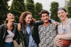 Quatre jeunes amis souriant ensemble Image stock