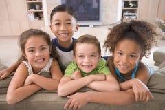 Quatre jeunes amis traînant à la maison Photos stock