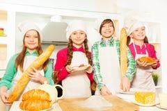 Quatre jeunes cuisiniers avec la nourriture de boulangerie à la cuisine Photographie stock libre de droits