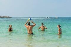 Quatre jeunes d'amusement jouent le volleyball sur la plage à la côte de Dubaï Émotions humaines positives, sentiments, joie Coup photographie stock libre de droits
