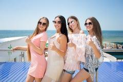 Quatre jeunes femmes attirantes se tenant sur un fond de station de vacances Dames de sourire en vêtements sport et verres de sol photographie stock