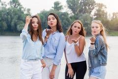 Quatre jeunes femmes attirantes tenant et envoyant des baisers à l'appareil-photo extérieur arbres et rivière au fond photo stock