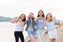 Quatre jeunes femmes dans le studio se tenant au coeur de ligne et d'exposition font des gestes ainsi que des bras extérieurs image libre de droits
