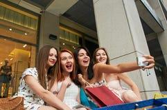 Quatre jeunes femmes faisant des emplettes au mail prenant un selfie Image libre de droits