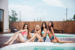 Quatre jeunes femmes mignonnes de sourire s'asseyant près de la piscine Images stock