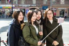Quatre jeunes filles des touristes de l'Asie sont photographiées contre Photo stock