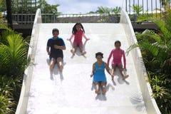 Quatre jeunes filles heureuses sur la glissière d'eau Photo libre de droits