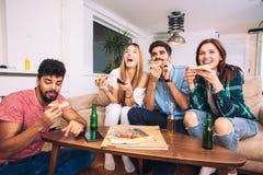 Quatre jeunes gais mangeant de la pizza à la maison Photos stock