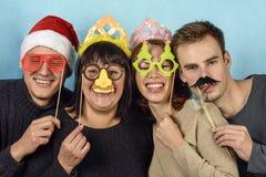 Quatre jeunes hommes dans les masques de fête Photo stock