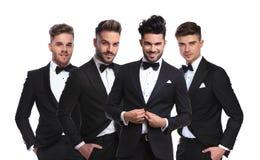 Quatre jeunes hommes dans les tuxedoes noirs se tenant ensemble Photo stock
