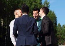 Quatre jeunes hommes parlant entre eux et riant Image libre de droits
