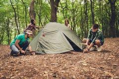 Quatre jeunes meilleurs amis gais installent une tente dans la forêt Photo stock