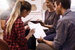 Quatre jeunes professionnels en session de séance de réflexion Images stock