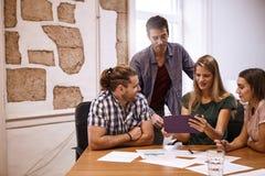 Quatre jeunes professionnels lors de la réunion de séance de réflexion Images stock