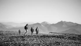 Quatre jeunes sportifs marchant sur la montagne rocheuse platon Photographie stock libre de droits