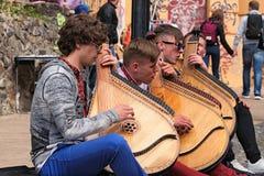 Quatre jeunes types jouent sur l'instrument folklorique national ukrainien, appelé bandura et chantent les chansons Descente du ` Images stock
