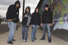 Quatre jeunes voleurs fâchés avec des couteaux Images stock