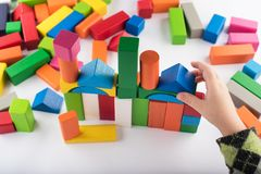 Quatre jeux de fille d'ans dans le concepteur Jouets en bois, concepteur coloré du ` s d'enfants sur le fond blanc, divertissemen photographie stock libre de droits