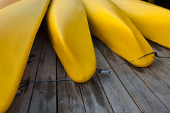 Quatre kayaks jaunes sur un dock Photos libres de droits