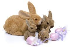 Quatre lapins de Pâques devant des oeufs Photo stock