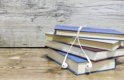 Quatre livres et écouteurs sur le fond en bois image stock