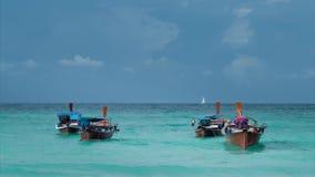 Quatre long-ont coupé la queue le bateau balançant dans les vagues bleues, bateau à voile blanc sur l'horizon, Koh Lipe Thailand banque de vidéos