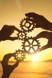 Quatre mains du ` s d'hommes d'affaires rassemblent un puzzle des vitesses contre le coucher du soleil images stock