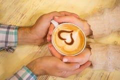 Quatre mains enroulées autour d'une tasse de café Photo stock