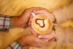 Quatre mains enroulées autour d'une tasse de café Photos libres de droits
