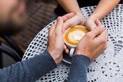 Quatre mains enroulées autour d'une tasse de café Images stock
