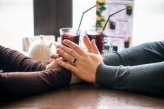 Quatre mains enroulées autour d'une tasse de café avec le dessin de coeur Photographie stock