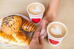 Quatre mains enroulées autour d'une tasse de café avec le dessin de coeur Photo libre de droits