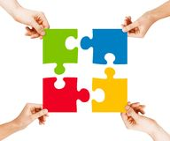 Quatre mains reliant des morceaux de puzzle Photos libres de droits