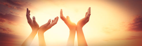 Quatre mains sur le coucher du soleil Image libre de droits