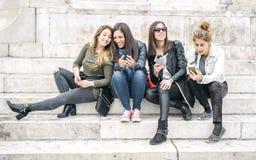 Quatre medias sociaux de observation heureux d'Internet d'amie dans le smartp Photo stock