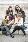 Quatre medias sociaux de observation heureux d'Internet d'amie dans le smartp Image stock