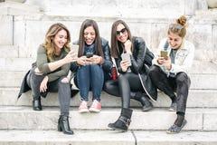 Quatre medias sociaux de observation heureux d'Internet d'amie dans le smartp photos stock