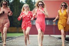 Quatre meilleurs amis riant et courant au lac Image stock